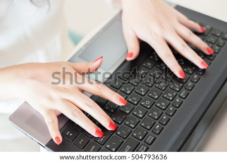 woman's hands are typing on a computer keyboard. Young businesswoman sitting at office and working on presentation. her hands with a red nail Polish