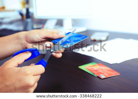 Woman's hands cutting bank card with scissors on wooden table background - stock photo