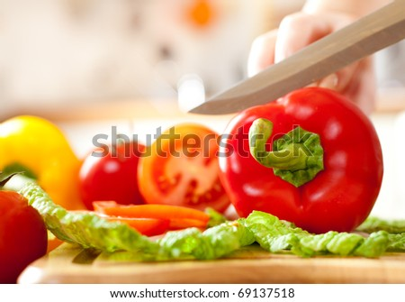 Woman's hands cutting tomato bell pepper, behind fresh vegetables. - stock photo