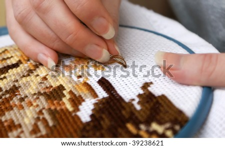 Woman's hands embroidering a picture (cross-stitch) - stock photo