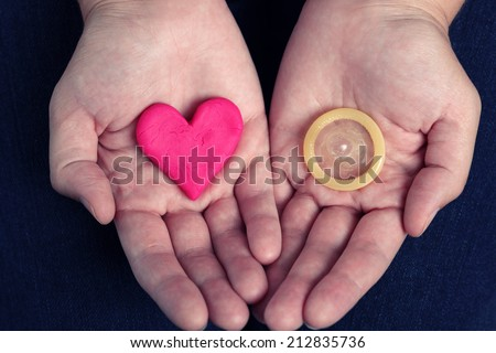Woman's hands hold a heart shape and a condom. Concept image. - stock photo
