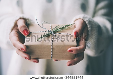 Woman's hands hold christmas or new year decorated gift box. Toned picture - stock photo