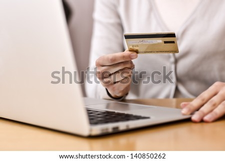 Woman's hands holding a credit card and using computer keyboard for online shopping - stock photo
