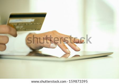 Woman's hands holding a credit card and using tablet pc for online shopping