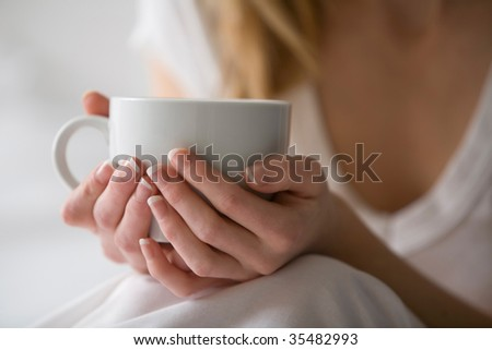 Woman's hands holding a cup