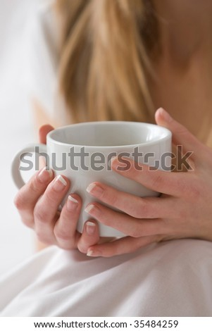 Woman's hands holding a white mug - stock photo