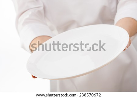 Woman's hands holding an empty plate on white background - stock photo