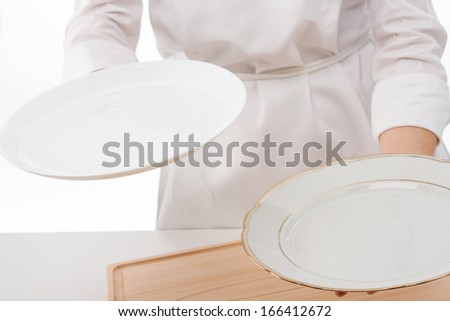 Woman's hands holding an empty plates on white background - stock photo