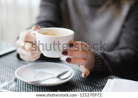Woman's hands holding cup of coffee - stock photo