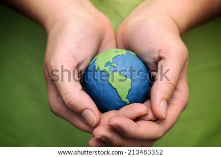 Woman's hands holding plasticine planet (Child's play clay). Elements of this image furnished by NASA. - stock photo