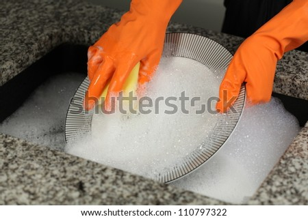Woman's hands in gloves cleaning a plate - stock photo