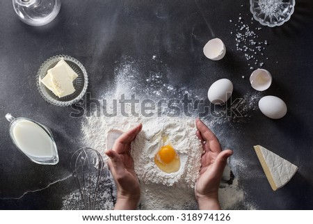 Woman's hands knead dough on table with flour, eggs and ingredients. Top view. - stock photo
