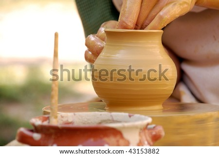 Woman's hands on a piece of pottery made of clay on a rotating wheel.