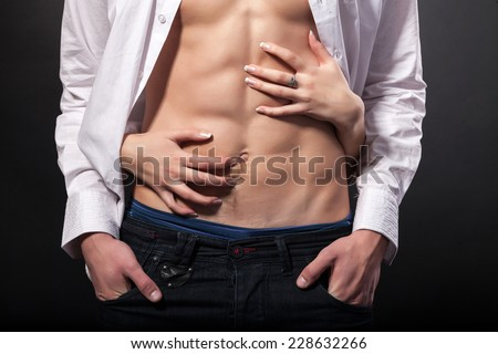 Woman's hands on a sexy man's torso on a black background - stock photo