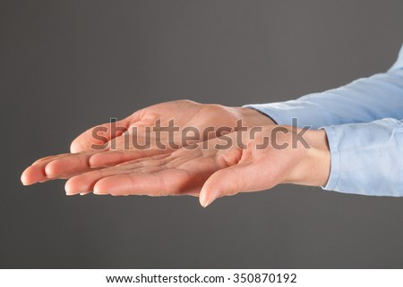 Woman's hands outstretched, grey background
