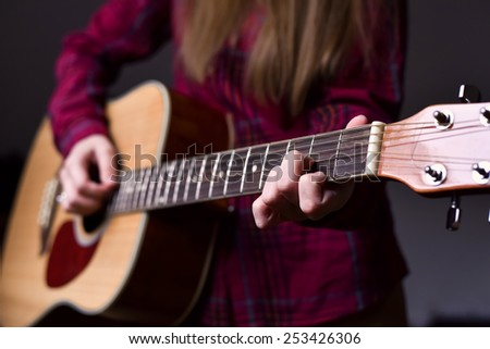 woman's hands playing acoustic guitar, close up. Playing acoustic guitar girl or woman with long hair by fingers. finger position on the chord. selective focus image - stock photo