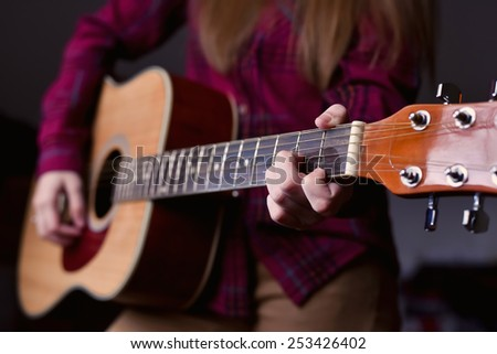 woman's hands playing acoustic guitar, close up. Playing acoustic guitar girl or woman with long hair by fingers. finger position on the chord. selective focus image