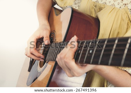 woman's hands playing guitar, close up. Vintage tone - stock photo