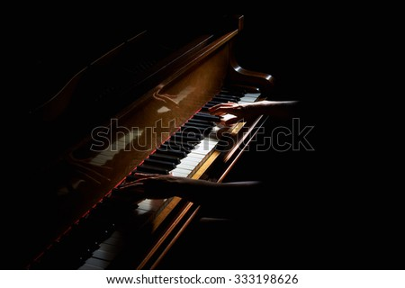 Woman's hands playing on the keyboard of the piano in night closeup - stock photo
