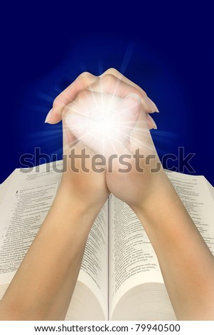 woman's hands praying next to the Bible - stock photo