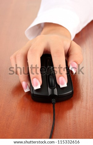 woman's hands pushing keys of pc mouse, on wooden table close-up