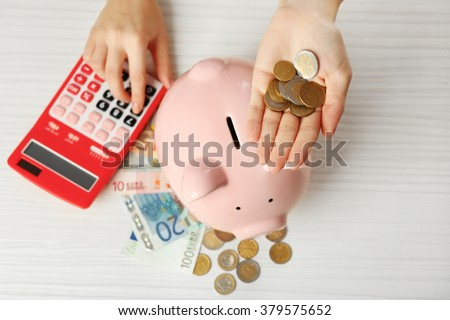 Woman's hands putting euro coin into a piggy bank and counting with calculator on the table. Financial savings concept - stock photo