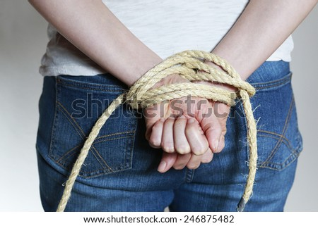 woman�´s hands tied with a rope