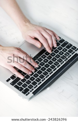 Woman's hands typing on a laptop keyboard