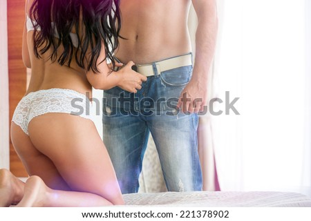 woman's hands unbuttons jeans of handsome man in bedroom - stock photo