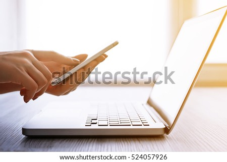 Woman's hands using mobile phone and laptop at the office