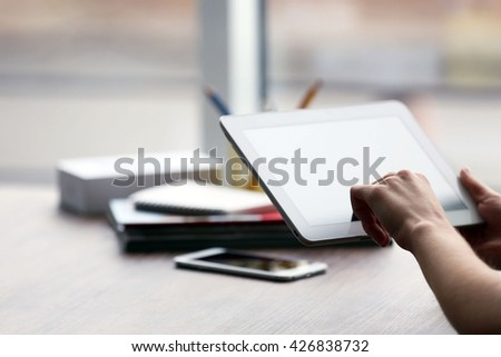 Woman's hands using tablet at the table