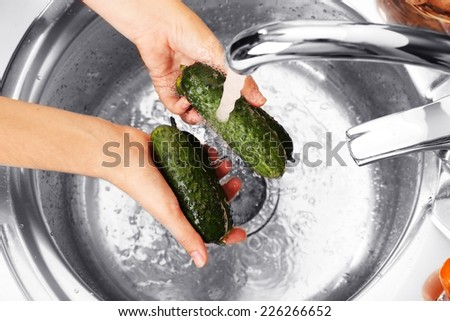 Woman's hands washing cucumbers in sink - stock photo