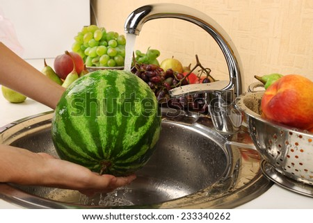 Woman's hands washing watermelon and other fruits in colander in sink - stock photo