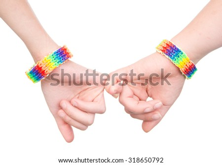 woman's hands with a bracelet patterned as the rainbow flag holding on to little fingers - stock photo