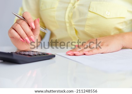 Woman's hands with a calculator and a pen in office