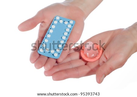 woman's hands with birth control pills and condom - stock photo