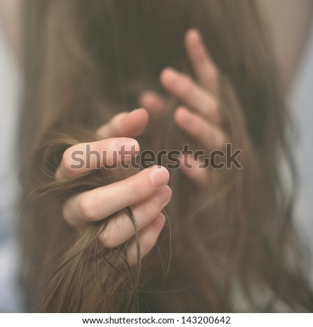 woman's hands with long hair, the concept of sadness depression - stock photo