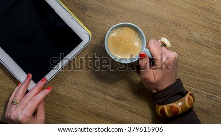 woman's hands with nail polish holding coffee and tablet