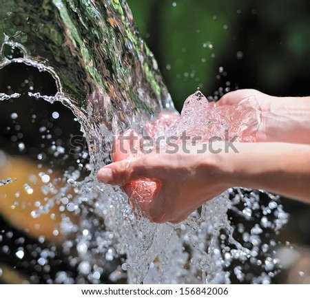 Woman's hands with water splash - stock photo