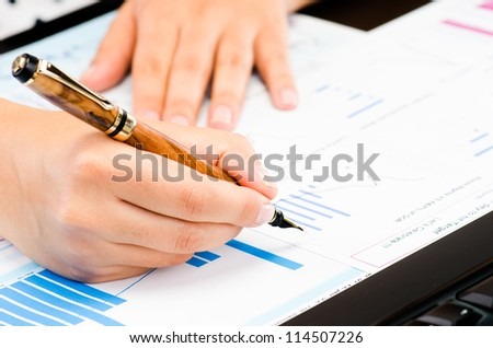 Woman's hands working on business reports at office - stock photo