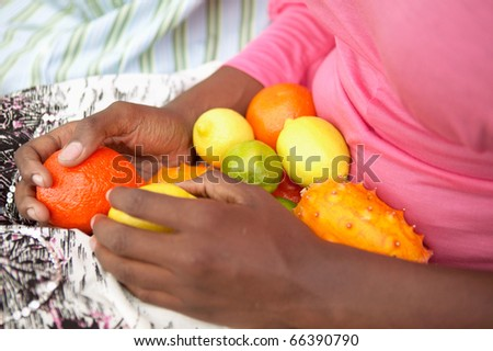 Woman's lap filled with fresh fruit - stock photo