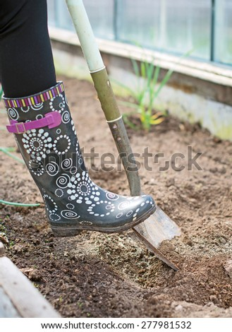 Woman's leg digging soil in greenhouse. - stock photo