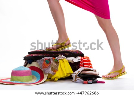Woman's leg on filled suitcase. Legs in yellow flip flops. Fashion is everything. It's not that simple. - stock photo