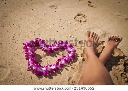 Woman's legs and purple orchid lei on white sand beach, Hawaii, Oahu - stock photo