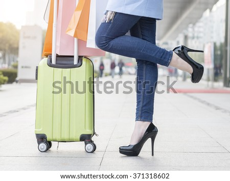 Woman's legs and travel suitcase