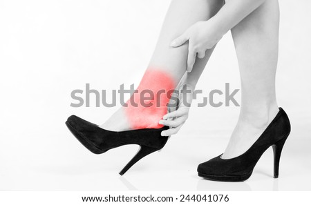 Woman's legs ankle pain in high heels - stock photo