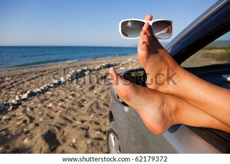 Woman's legs dangling out a car window parked at the beach - stock photo