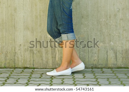 Woman's legs in jeans rolled up - stock photo