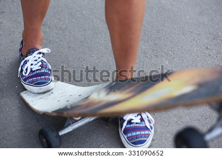 Woman's legs on skating board on the road