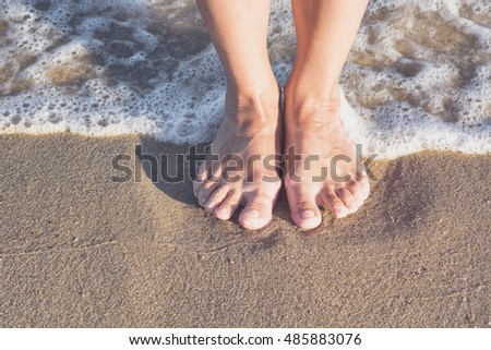 Woman's legs on the sand beach and sea waves at sunset.